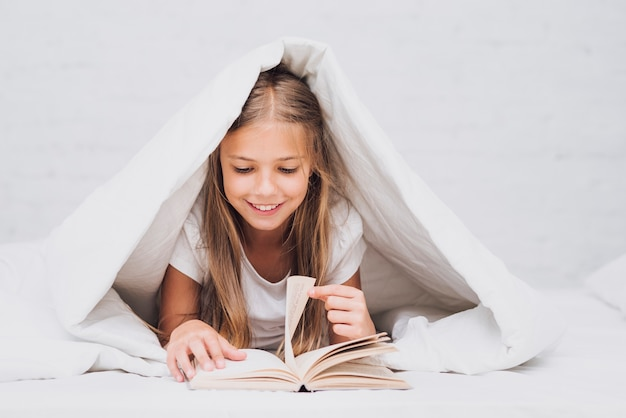 Little girl under the blanket reading a book