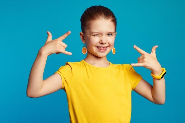 Маленькая девочка моргает и показывает знак рок-н-ролла с высунутым языком