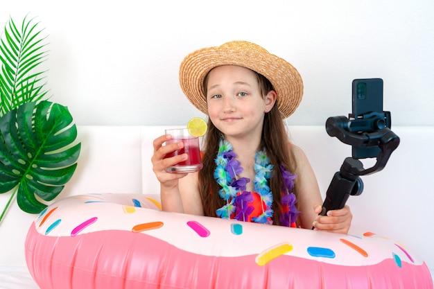 Маленькая девочка-блогер имитирует отдых на домашнем карантине и снимает видео на телефон.
