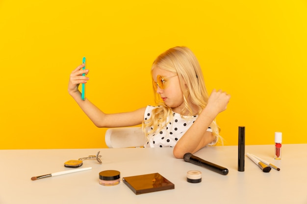 비디오를 만드는 카메라 앞에서 노란색 스튜디오에서 어린 소녀 블로거. 블로거로 일하면서 인터넷 용 비디오 튜토리얼 녹화.