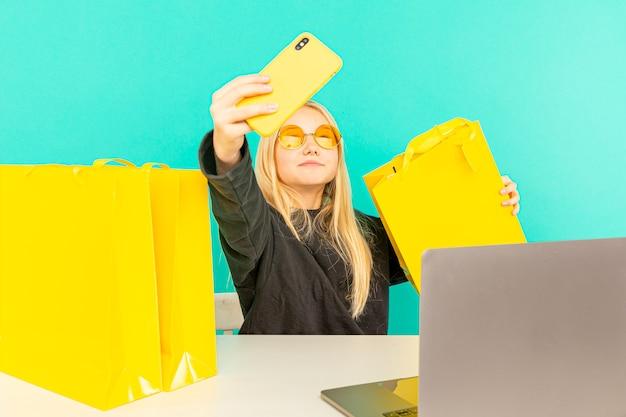 어린 소녀 블로거는 밝은 파란색 배경에 스마트 폰을 사용하여 기록 된 온라인 리뷰를 작성합니다.