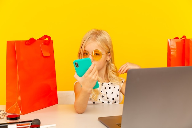 Little girl blogger with blue phone making video for blog and followers sitting in the yellow studio isolated.