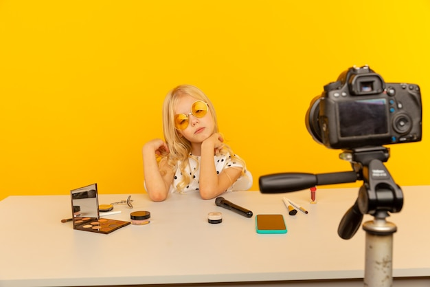 Little girl blogger in the yellow studio in front of camera making video. working as blogger, recording video tutorial for internet.