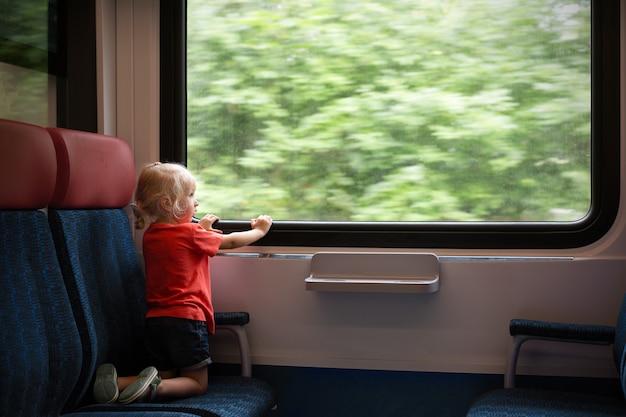 기차로 여행하는 어린 소녀 금발 머리. 소녀는 창을 통해 찾고 있습니다. 대중교통