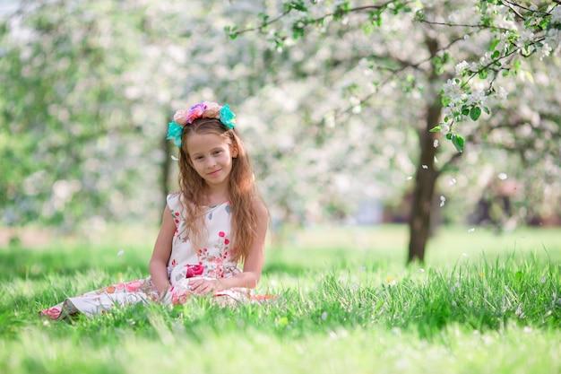 Little girl in blooming cherry tree garden outdoors