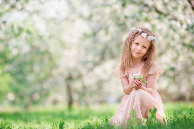 Little girl in blooming cherry tree garden outdoors