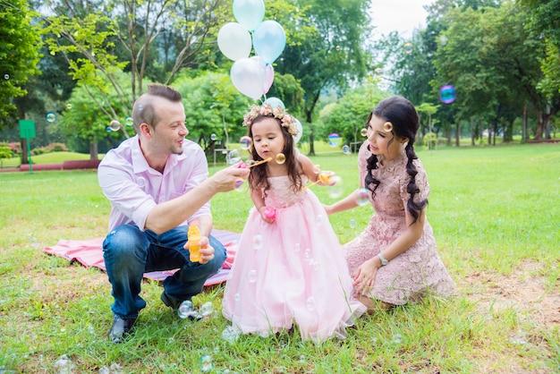Маленькая девочка дует пузыри с отцом и матерью в парке
