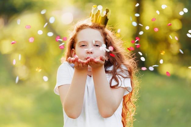 Маленькая девочка дует конфетти из ее руки