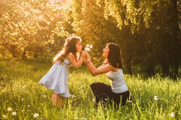 Little girl blowing dandelion in park with her mother