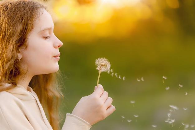 Little girl blowing dandelion in spring park medical healthy concept