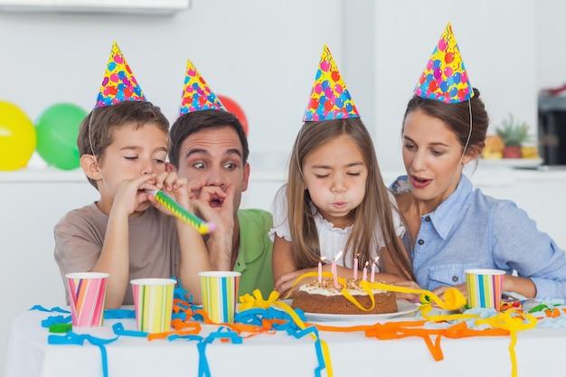 Маленькая девочка, дует ее свечи во время ее дня рождения