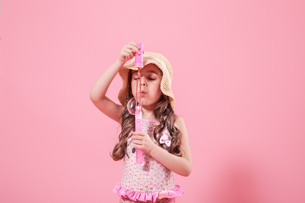 Little girl blowing soap bubbles on colored background