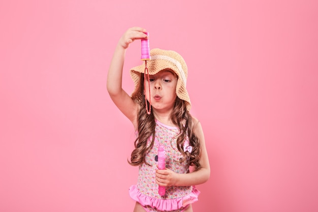色の壁にシャボン玉を吹く少女