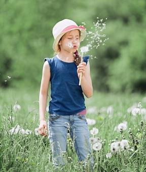 緑の牧草地に立っているタンポポを吹く少女