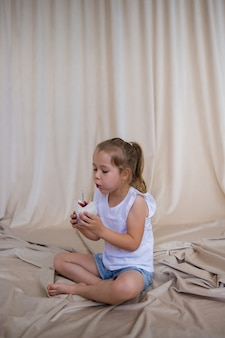 A little girl blows out a candle on a cake on a beige background with space for text