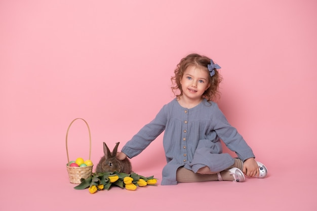 Little girl in blu dress with rabbit, tulips, basket with colorful eggs on pink