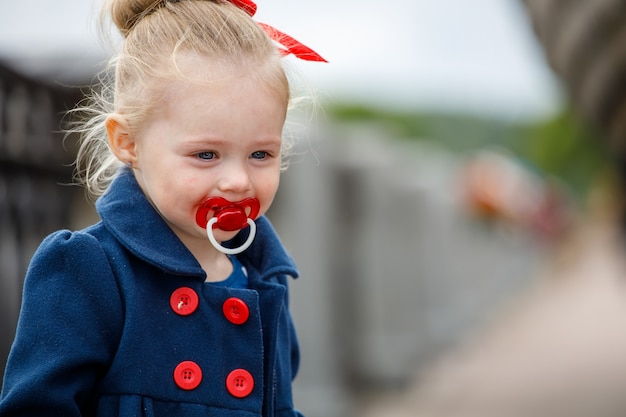 Little girl in a blue coat with a pacifier in her mouth on the street