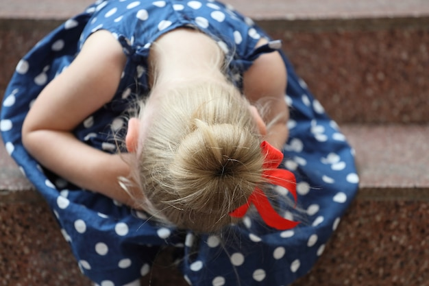 Little girl in a blue dress sits on the steps and cries