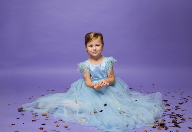 A little girl in a blue puffy dress sits on the floor with confetti on purple