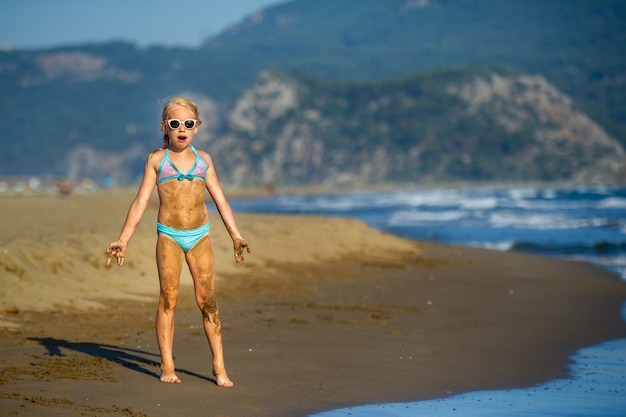 A little girl in a blue swimsuit and dirty stands on a mediterranean beach in turkey.