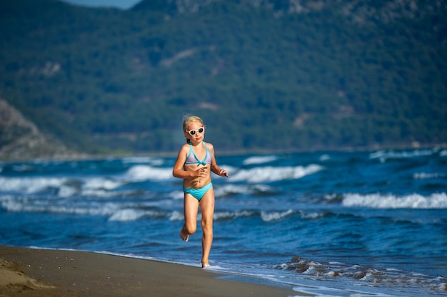 A little girl in a blue swimsuit and glasses runs on a mediterranean beach in turkey.