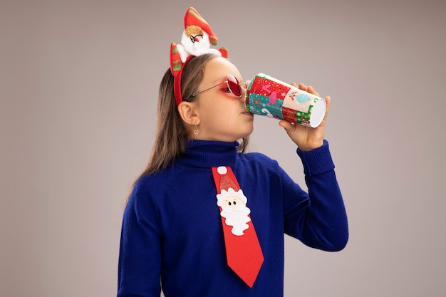 Little girl in blue turtleneck wearing funny christmas rim on head drinking from colorful paper cup   standing over white wall