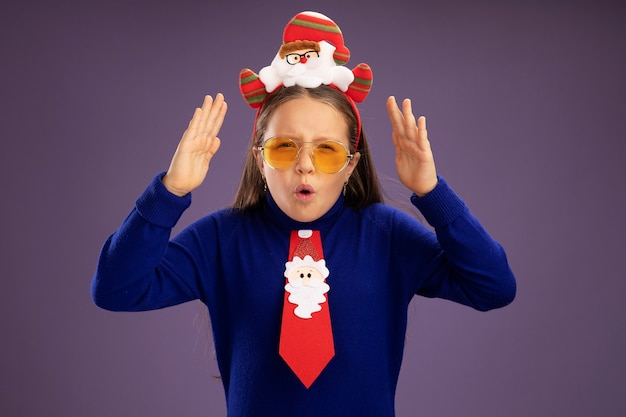 Little girl in blue turtleneck with red tie and  funny christmas rim on head amazed and surprised with arms raised