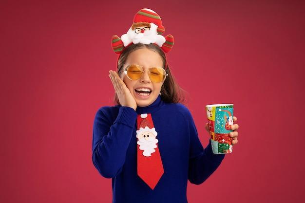 Bambina in dolcevita blu con cravatta rossa e divertente bordo natalizio sulla testa che tiene in mano una tazza di carta colorata che sembra felice ed eccitata in piedi sul muro rosa