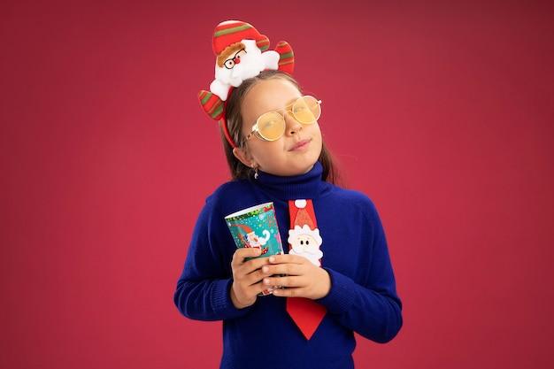 Bambina in dolcevita blu con cravatta rossa e bordo divertente di natale sulla testa che tiene il bicchiere di carta colorato con espressione sicura