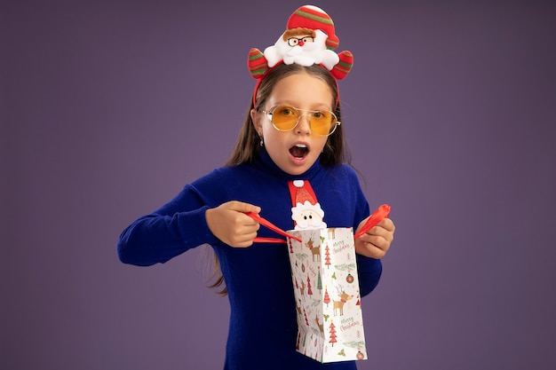 Little girl in blue turtleneck with red tie and  funny christmas rim on head holding paper bag with christmas gift   happy and surprised  standing over purple wall