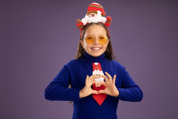 Little girl in blue turtleneck with red tie and  funny christmas rim on head looking at camera smiling cheerfully making heart gesture with fingers standing over purple background