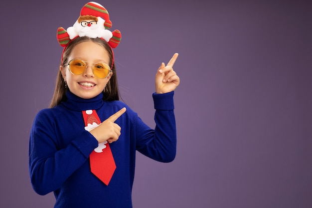 Little girl in blue turtleneck with red tie and  funny christmas rim on head looking at camera smiling cheerfully pointing with index fingers to the side  standing over purple background