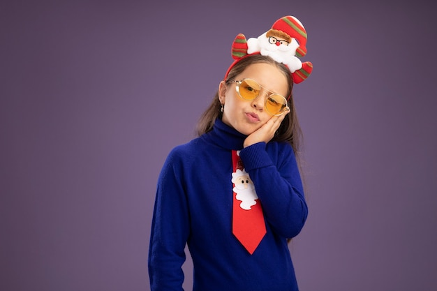 Little girl in blue turtleneck with red tie and  funny christmas rim on head looking at camera tired and bored  standing over purple background