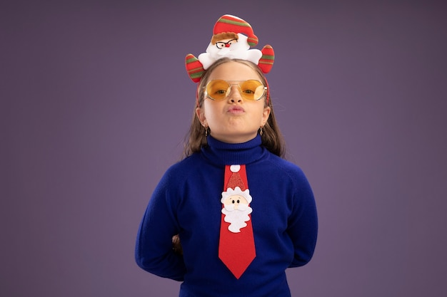 Little girl in blue turtleneck with red tie and  funny christmas rim on head  with confident expression  standing over purple wall