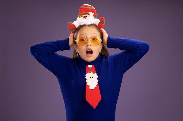 Bambina in dolcevita blu con cravatta rossa e bordo divertente di natale sulla testa preoccupata e sorpresa con le mani sulla sua testa