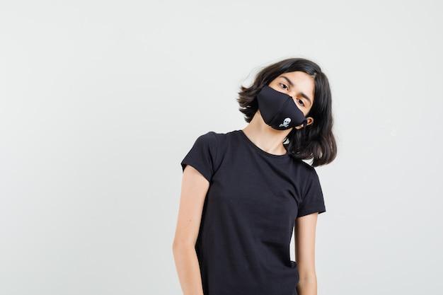 Маленькая девочка склоняет голову на плече в черной футболке, маске, вид спереди.