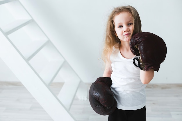 Little girl in boxing gloves. winner.