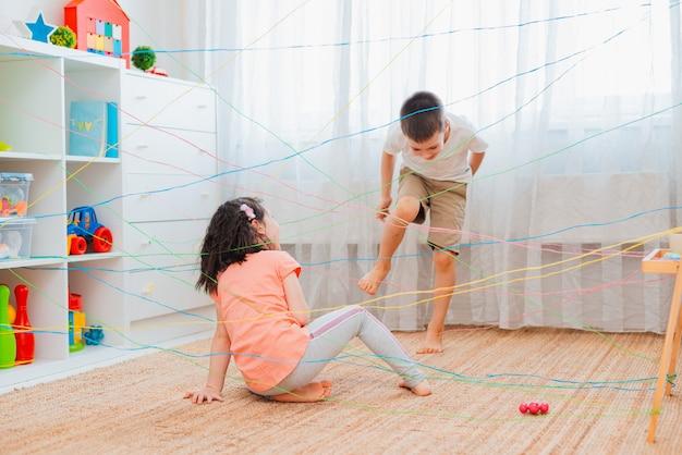 Маленькая девочка, мальчик, брат, братья и сестры, друзья-дети лезут через веревочную паутину, квест с игровыми препятствиями в помещении.