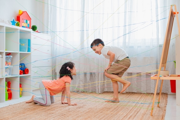 Little girl boy brother, siblings, friendschild climbs through rope web,  game obstacle quest indoors.