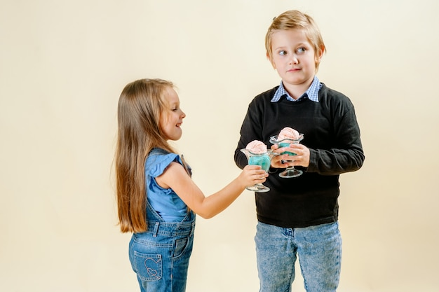 Little girl and boy eat ice cream on a light background