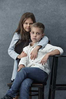 Little girl and a boy on gray