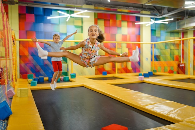 Little girl and boy having fun on kids trampoline, playground in entertainment center.