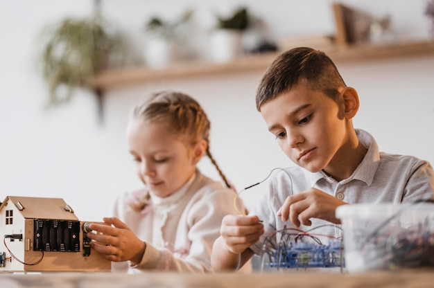 Little girl and boy looking at electrical devices