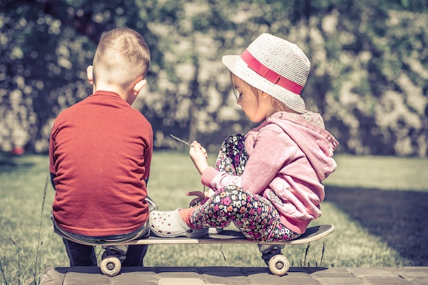 Little girl and boy playing on skateboard, concept of childhood friendship