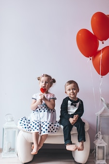 Little girl and boy sitting on a white chair near heart-shaped balloons.