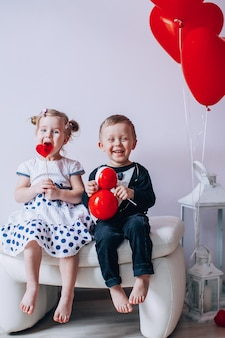 Little girl and boy sitting on a white chair near heart-shaped baloons. girl licking a red lollipop. valentines day concept.
