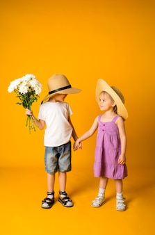Little girl and a boy in straw hats hold hands on a yellow surface with space for text. a boy holds a bouquet of white flowers