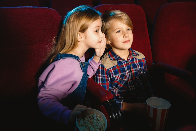 Little girl and boy watching a film at a movie theater