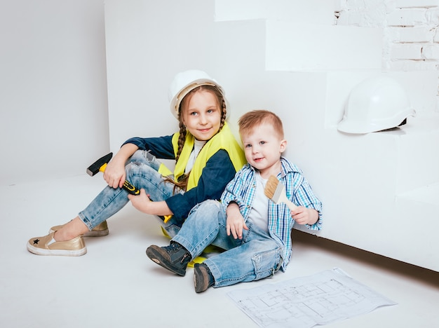 Little girl and boy on the white background. construction