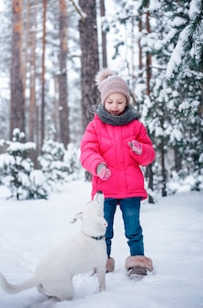 Little girl in a bright jacket plays in the winter snowy forest with her dog jack russell terrier